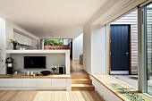 Open-plan interior with TV on half-height wall, wooden steps leading to dining area and open sliding doors leading to terrace