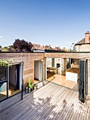Wooden terrace of contemporary house with wood-clad facade; view into kitchen through open folding doors