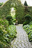 Cobbled path leading through topiary bushes to archway in hedge