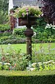 Im Beet stehende Stele mit Metall Pflanzengefäss im Vintage Stil