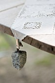 Tablecloth weight with granite pebble hung from lace tablecloth