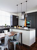 Dining area with retro metal chairs in front of free-standing counter in open-plan fitted kitchen with dark grey cabinet fronts