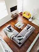 View down onto grey corner sofa and coffee table on dark parquet floor; yellow designer armchair and standard lamp in corner
