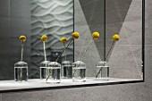 Gelbe Blumen in Glasvasen vor Spiegel in Wandnische