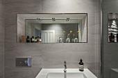 Washbasin on tiled wall below mirror in niche