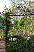 Idyllic seating area with metal furniture below climbing roses on gazebo