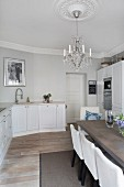 White country-house kitchen and modern dining area in period apartment with chandelier hanging from stucco ceiling rose