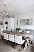 Upholstered chairs and bench around chunky table in open-plan kitchen.dining room with chandelier hanging from ceiling rose