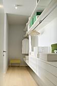 Blick durch offene Tür in Ankleide mit offenem Kleiderschrank und Schubladenmodule in Weiss