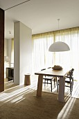 Pendant lamp with white lampshade above pale wood dining table and chairs in front of sunlit glass wall with closed curtain; partition screening kitchen to one side