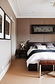 Double bed with headboard under framed picture on upholstered wall and leather stool at foot end in bedroom