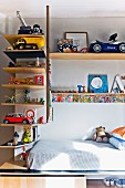 Toys on L-shaped shelves above mattress on wooden base in child's bedroom