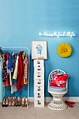 Clothes hanging on rail next to stack of white storage boxes and wicker chair under illuminated neon lettering on wall painted light blue