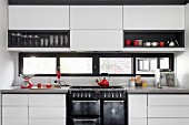 Modern fitted kitchen with white, touch-open fronts and black accents provided by niche interiors and window frames