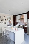Glossy, white counter with sink and plexiglass stools; fitted kitchen with dark fronts and scattered gallery of photos in background