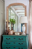 Shabby chic lamp, carved candlesticks and mirror on vintage chest of drawers painted turquoise