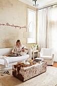 Schrift-Installation an sandfarbiger Wand über Sofa mit weisser Husse und Ottomane mit Tierfellbezug; lesende Frau auf Sofa