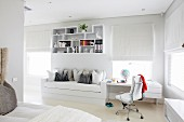 Fitted couch and desk as space-saving solution below decorative wall-mounted shelves in white, teenager's bedroom