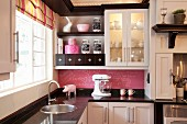 Black and white fitted kitchen with striped Roman blind and pink blackboard splashback