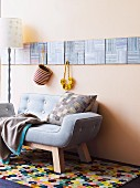 Two-seater pastel sofa on brightly patterned rug below square textured pictures on wall