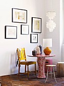 Vases and table lamp on table covered in floral wallpaper and various chairs below framed pictures on white wall