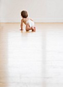 Baby crawling on hardwood floor