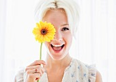 Portrait of blonde woman holding yellow flower