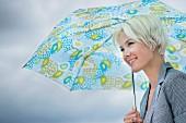 Blonde woman holding umbrella