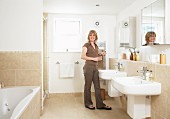 Woman in bathroom with twin sinks below mirrored cabinets and sand-coloured tiles on floor and walls