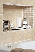 Sand-coloured tiles on wall and in niche with toiletries above bathtub