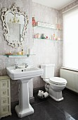 A light bathroom with an elaborate mirror and traditionally patterned wallpaper