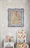 The word PEACE, jewellery hanging in a picture frame and a floral patterned antique chair in a romantic bathroom