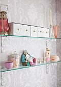 Row of vintage drawers, Chinese porcelain figurine and various knickknacks on glass shelves in shabby chic bathroom