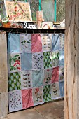 Patchwork curtain made from fabric remnants with colourful patterns and old prints of plants and butterflies hiding shelves of utensils in greenhouse