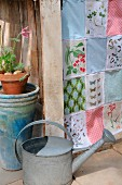 Patchwork curtain made from fabric remnants with colourful patterns and vintage prints of plants and butterflies; watering can in foreground
