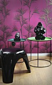 Sculptures on tray tables and retro plastic stool in front of mauve wallpaper