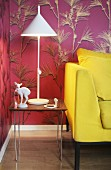 Yellow sofa and knick-knacks and lamp on side table against mauve wallpaper