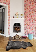 Animal-skin rug in front of fire in corner stove and pink, floral wallpaper in country-house interior