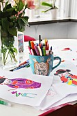Colourful drawings of geisha and mug of pens on table