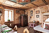 Wood-panelled dining room with antique, peasant-style furniture, bench around stove and set table in foreground