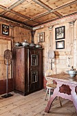 Antique, farmhouse furniture and religious pictures in artistically wood-panelled dining room