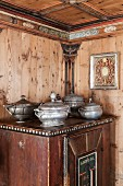 Pewter tureens on old farmhouse cupboard in wood-panelled dining room