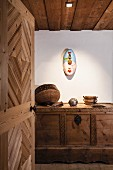 View through open wooden door of modern, painted wall-mounted sculpture and ornaments on carved farmhouse trunk