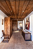 Contemporary art and antique, rustic hall furnishings (plank chair, wardrobe and trunk) in hallway