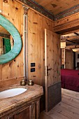 Rustic washstand and oval mirror with wooden frame stained turquoise; view into bedroom through open bathroom door