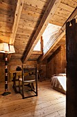 Artistically crafted standard lamp and simple workspace below wood-panelled sloping ceiling in chalet