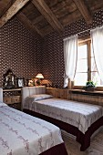Textile wallpaper with geometric pattern in attic guest room with twin beds and romantic ambiance in restored chalet
