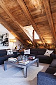 Sofa set and coffee table under sloping, rustic, wood-panelled ceiling