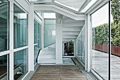 Porch of contemporary penthouse with terrace; staircase in background behind glass panel