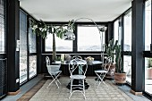 Seating area with delicate, white metal chairs and arc lamp in black conservatory of penthouse apartment